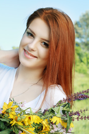 Portrait of the young beautiful woman outdoors photo
