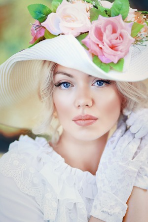 portrait of beautiful woman in victorian age dress and fancy hat with flowers