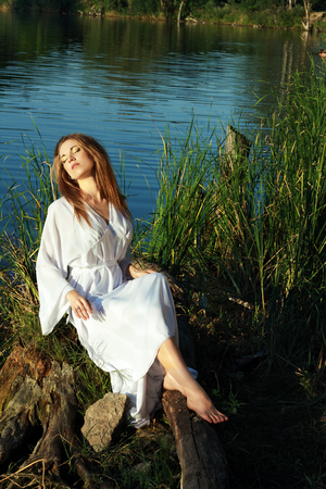 portrait of beautiful young woman in white dress resting on the lakeshore sitting surrounded with green grass photo