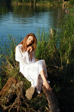 portrait of young woman in light white dress sitting at lakeshore surrounded by green grass photo