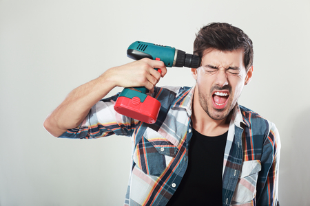 portrait of young man screaming holding drill near his head posing next to color background Stock Photo