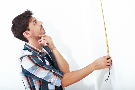 half length portrait of young man with tape measure doing repairs standing next to white background