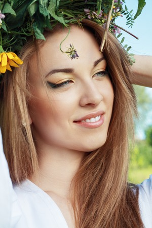outdoor portrait of beautiful young woman wearing wreath on her head photo