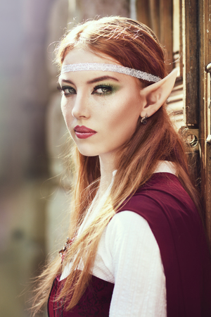 Elf girl on the rock in red cloak posing outdoor