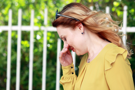 woman sneezing outdoor summer time allergy conept