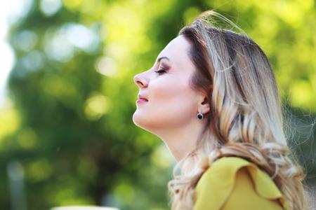 夏の公園でブロンドの髪と美しい女性 写真素材