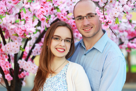 happy couple under blossom spring tree