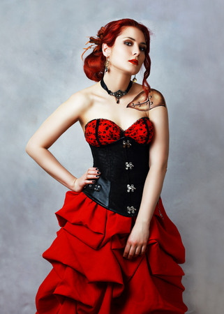 cooper: beautiful steampunk girl with bodypainting on her shoulder posing at studio in black corsette and red skirt