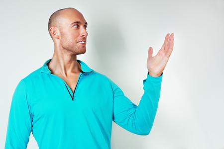 녹청 스포츠 자 켓 서 잘 생긴 남자 againts 벽을 서 서 그의 손으로 뭔가 보여주는, 가리키는 스톡 콘텐츠