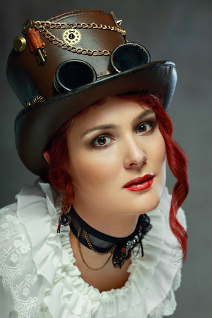 steampunk goggles: portrait of beautiful steampunk woman wearing vintage hat posing next to color background