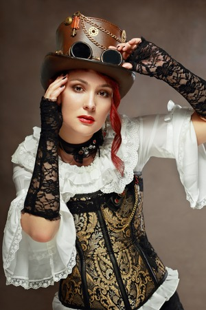 steampunk goggles: portrait of beautiful steampunk woman wearing vintage hat and corset posing next to color background
