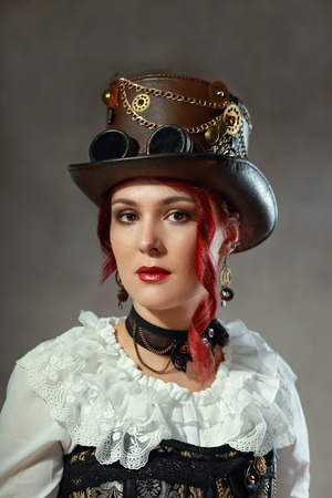 steampunk goggles: portrait of beautiful steampunk woman wearing corset and vintage hat posing next to color background