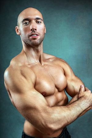 portrait of young strong muscular man with bared torso standing next to color backgtound