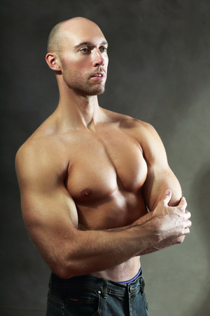 sixpack: handsome athlete man show his biceps over dark studio background