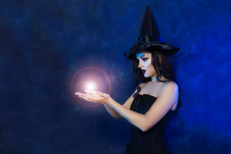 half length portrait of beautifull young woman in witch dress posing next to color background Stock Photo