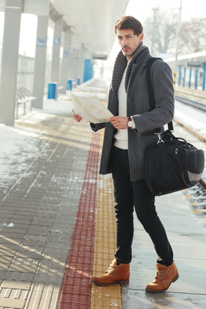 outdoor portrait of young handsome man standing at train station holding map in hands wearing warm coat Stock Photo