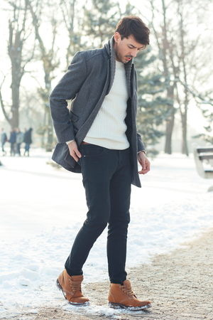 outdoor portrait of young handsome man in warm coat walking alone in snowy park