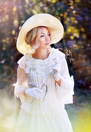 Portrait der schönen Frau im Victorianalterkleid und im fantastischen Hutgehen im Freien