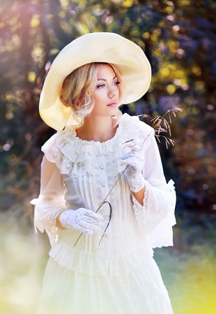 portrait of beautiful woman in victorian age dress and fancy hat walking outdoor