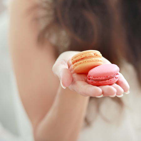 woman holding macaroons in her head, shallow depth