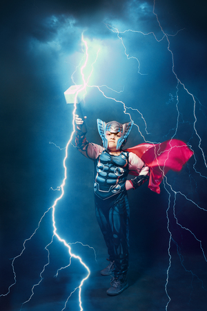 little boy in thor costume with lightnings and thunder epic Banque d'images