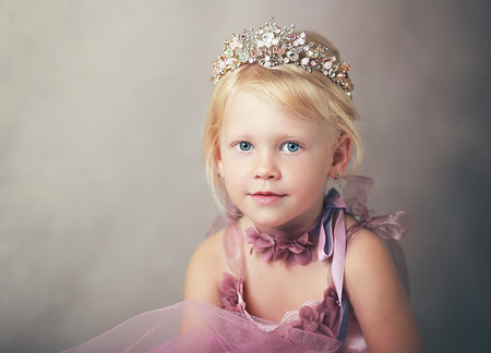 beautiful girl little princess in pink dress holing crown in her hands