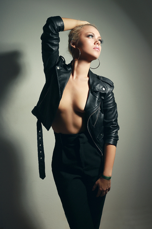 beautiful young woman posing bare shoulders in black leathure jacket