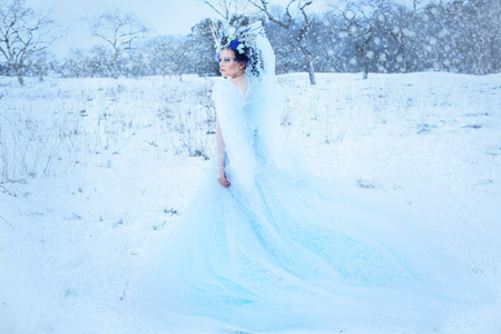 beautiful winter fairy in crown and light blue dress walking over snow field Snow Queen concept 免版税图像