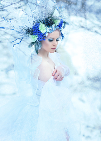 beautiful winter fairy in crown and light blue dress walking over snow field Snow Queen concept Stock fotó