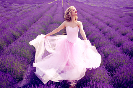 Beautiful woman in pink dress dancing in lavender field sunny summer Stock fotó