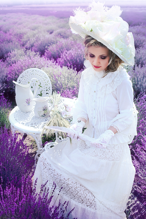Beautiful woman in Victorian vintage style outfit and hat sitting on lavender field Stock fotó