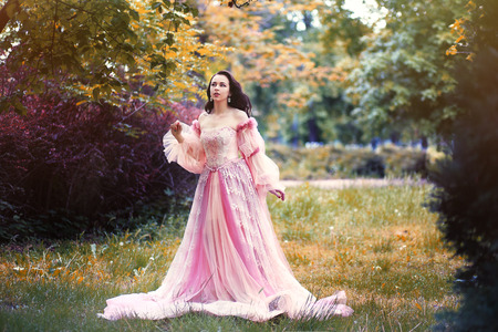 beautiful young woman in romantic pink dress gown in magic forest