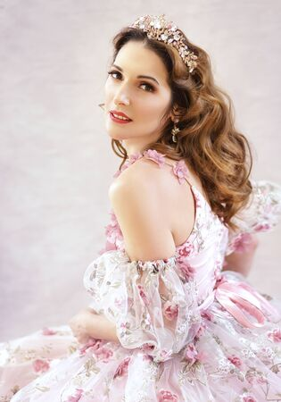 Beautiful middle age woman wearing evening gown with pink roses and crystal crown