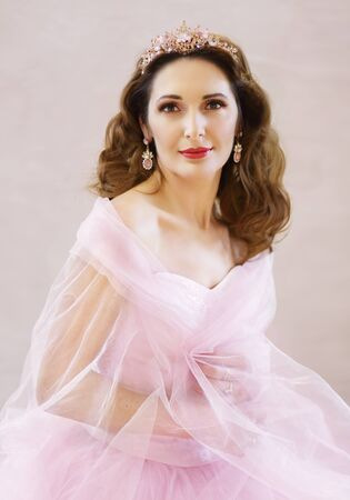 Beautiful woman in pink dress gown with tiara diadem on her head