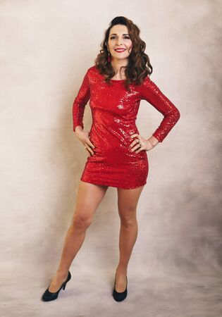 Beautiful middle age woman in short red dress full body
