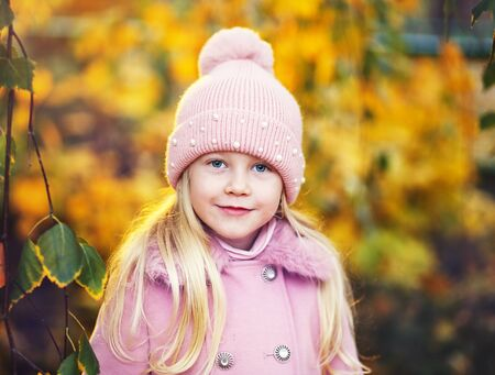 Portrait of beautiful little girl in pink hat and coat in autumn park