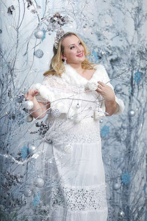 beautiful plus size woman woman in white dress as fairy queen in magic winter christmas forest