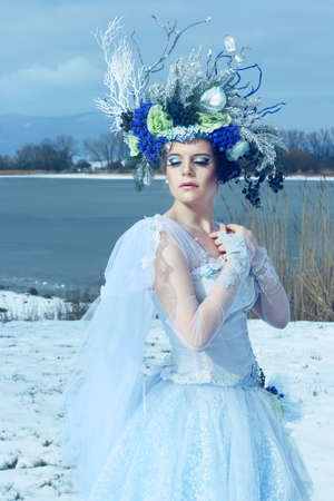 Winter fairy outdoor wearing bluish dress and floral crown