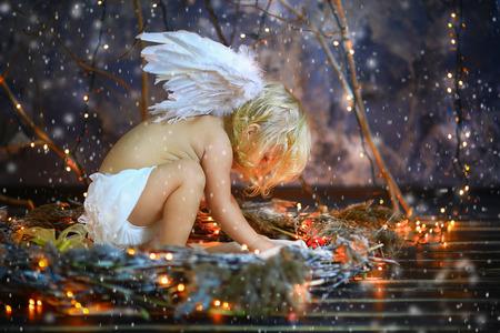 baby angel: la ragazza con le ali di un angelo nidi con lampadine rosse Archivio Fotografico