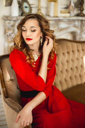 costume jewelry: The girl in a red dress with a black belt in gold costume jewelry sits near a brown sofa