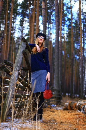 wearing spectacles: the girl wearing spectacles, in a blue sweater and a trouser skirt poses in the wood