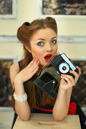 antiquarian: the girl in a dress in peas with red lipstick poses on the camera with the antiquarian camera