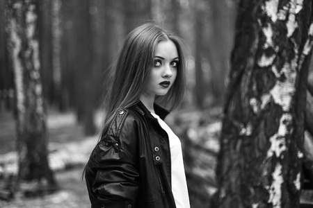 woman posing: the girl in a leather jacket the black-and-white photo, poses in the wood