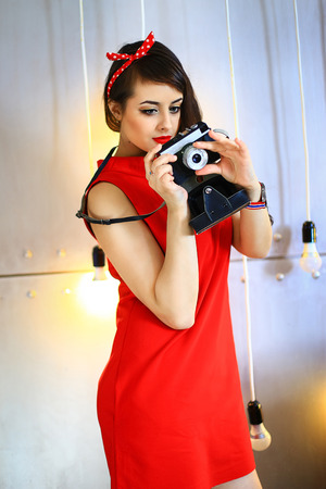 antiquarian: the brunette in a red dress poses on a gold background with the antiquarian camera Stock Photo