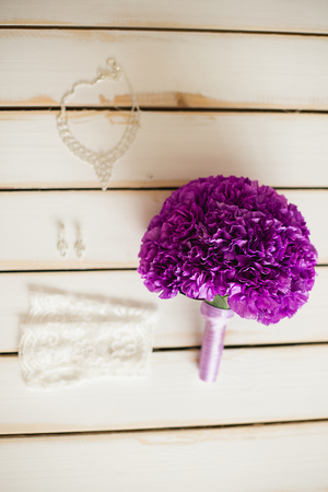 wedding: the violet bridal bouquet lies on a white timber floor nearby Stock Photo