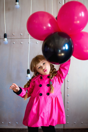 botas altas: the girl in a pink raincoat with balloons poses on the camera Foto de archivo