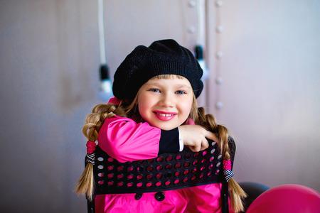 niñas sonriendo: la niña en un impermeable de color rosa y una boina negro posa en la cámara