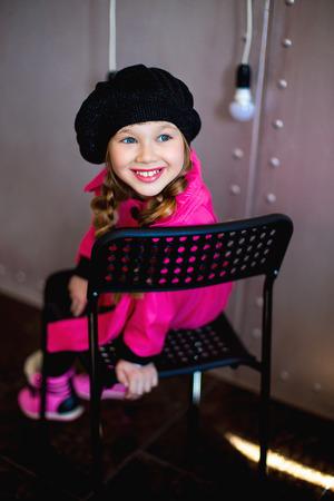botas altas: la niña en un impermeable de color rosa y una boina negro posa en la cámara