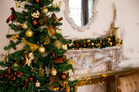 holiday decor: New Years and Christmas interior in gold color with a chimney portal, a fir-tree and gifts