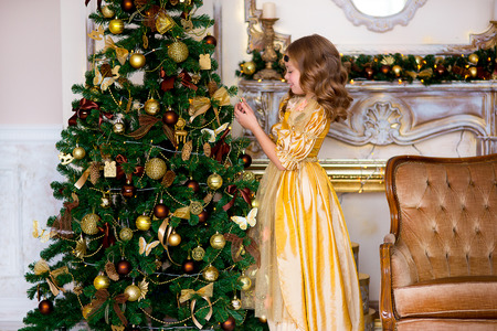 decorates: the girl in a gold dress decorates a New Year tree near a gold fireplace